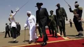 South Sudanese President Salva Kiir (C) walks with his Sudanese counterpart Omar al-Bashir (in white) before Kiir's departure from Khartoum, October 9, 2011.