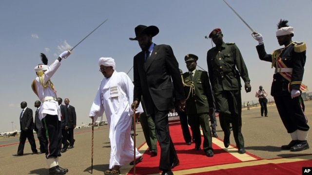 South Sudanese President Salva Kiir, center, walks with Sudanese counterpart Omar al-Bashir, Khartoum, Oct. 2011 (file photo).