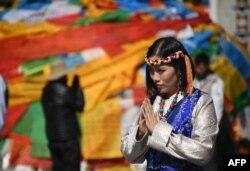 中国西藏自治区首府拉萨的大昭寺外面,一名穿着藏族传统服装的中国游客正在合什拍照(2016年9月10日)。