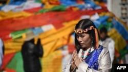 中國西藏自治區首府拉薩的大昭寺外面,一名穿著藏族傳統服裝的中國遊客正在合什拍照(2016年9月10日)。