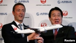 Japan Airlines President Yoshiharu Ueki (R) and Airbus Chief Executive Fabrice Bregier pose with a model of Japan Airlines' Airbus A350 airplane during their joint news conference in Tokyo, Oct. 7, 2013.