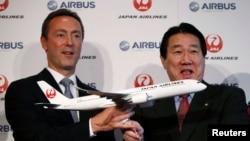 Pimpinan Japan Airlines Yoshiharu Ueki (kanan) and Pimpinan Eksekutif Airbus Fabrice Bregier berpose dengan model pesawat Airbus A350 dalam konferensi pers di Tokyo (7/10).