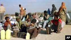 FILE - Somali refugees wait for a plane to take them home from Dabaab refugee camp in northern Kenya, Feb. 21, 2000.