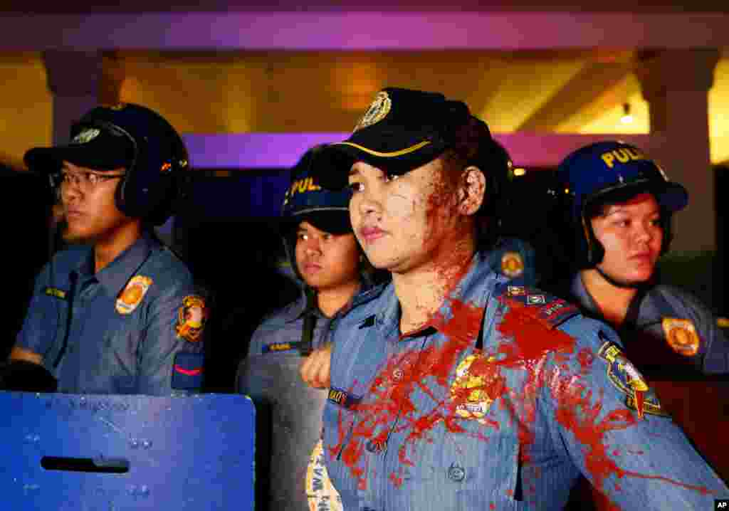 A police officer has her face and uniform splattered with red paint thrown by protesters during a rally at the U.S. Embassy in Manila to protest the recent Philippine Supreme Court's decision upholding the constitutionality of the Enhanced Defense Agreement or EDCA in the Philippines. The highest court's ruling effectively allows American forces, ships and planes to temporarily station in local military camps.