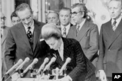 FILE - Then-Argentine President Isabel Peron signs government records after swearing in five new cabinet ministers in Buenos Aires, Argentina Aug. 11, 1975.