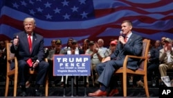 FILE - Republican presidential candidate Donald Trump gives a thumbs up as he speaks with retired Lt. Gen. Michael Flynn during a town hall in Virginia Beach, Va., Sept. 6, 2016.