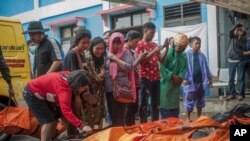 Beberapa warga berusaha mengidentifikasi jenazah untuk mencari anggota keluarganya yang masih hilang pasca tsunami di Pendeglang, Jawa Barat, Minggu (23/12).