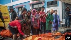 Los habitantes de la zona afectada buscan por sus familiares en los cadáveres de las víctimas del tsunami en Carita, Indonesia, el domingo 23 de diciembre del 2018.