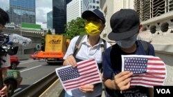 兩名香港市民7月4日美國獨立日手持A4紙印的美國國旗到美國領事館附近慶祝。(美國之音 湯惠芸拍攝)