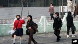 지난 4월 평양을 방문한 외신 기자단 버스를 향해 손을 흔드는 북한 여학생. 높은 구두로 멋을 냈다.