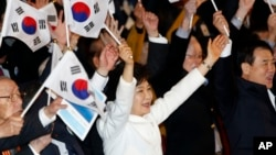 South Korean President Park Geun-hye, center, cheers with her national flag during a ceremony to celebrate the Independence Movement Day, in Seoul, March 1, 2014.