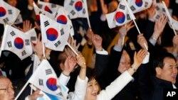 ປະທານາທິບໍດີເກົາຫຼີໃຕ້ ທ່ານນາງ Park Geun-hye (ກາງ) ພວມຍົກມືຊົມເຊີຍພ້ອມກັບທຸງຊາດໃນລະຫວ່າງພິທີສະຫຼອງ ວັນຂະບວນການເອກກະລາດ ຊຶ່ງເປັນວັນຄົບຮອບ ໃນ ການລຸກຮືຂຶ້ນຕໍ່ຕ້ານການປົກຄອງແບບອານານິຄົມຂອງຍີ່ປຸ່ນ ໃນປີ 1919 ທີ່ກຸງໂຊລ (1 ມີນາ 2014)