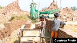 Two boys were placing bricks on a wooden cart at a brick factory in Cambodia. (Courtesy photo of Licadho)