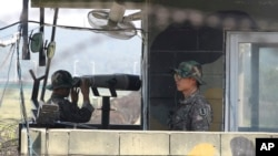 South Korean soldiers stand watch at a checkpoint in Paju, near the border with North Korea, in the wake of rocket and missile firings by Pyongyang into waters off the nation's east coast, Sept. 6, 2014.