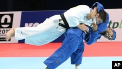 FILE - Luka Maisuradze of Georgia, top, competes against Saeid Mollaei of Iran during a men's -81 kilogram bronze medal match of the World Judo Championships in Tokyo, Aug. 28, 2019.