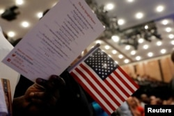 FILE - New citizens stand during a U.S. Citizenship and Immigration Services (USCIS) naturalization ceremony in Manhattan, New York, April 10, 2017.
