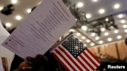 FILE - New citizens stand during a U.S. Citizenship and Immigration Services (USCIS) naturalization ceremony in Manhattan, New York, April 10, 2017. Three men were accused Tuesday of abusing a U.S. visa program and making false statements to the USCIS.