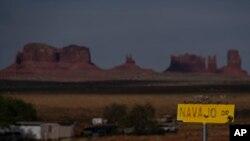 Tanda kawasan Navajo Drive, dengan Sentinel Mesa, rumah dan bangunan lain di Oljato-Monument Valley, Utah, terlihat dari kejauhan, 30 April 2020. (Foto: dok)