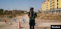"""Cảnh sát Trung quốc canh gác một trục lộ gần """"trung tâm huấn nghiệp"""" dành cho người Uighur ở Yining , KhuTự trị Uighur ở Tân Cương, 4/9/2018."""