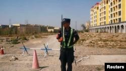 一名中國警察守在新疆伊寧一處官方所說的職業技能教育培訓中心外的路口。(2018年9月4日)