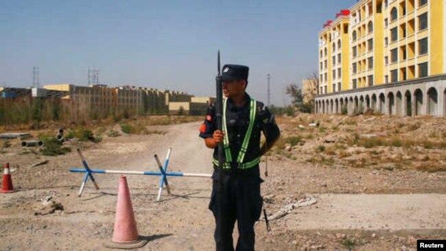 资料照片:一名中国警察守在新疆伊宁一处官方所说的职业技能教育培训中心外的路口。(2018年9月4日)