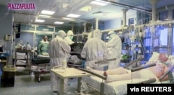 Medical staff in protective suits treat coronavirus patients in an intensive care unit at the Cremona hospital in northern Italy, in this still image taken from a video, March 5, 2020.