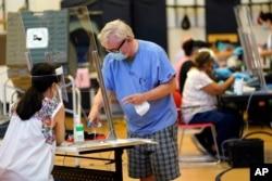 14일 미국 텍사스주 휴스턴에서 유권자가 투표를 하기 전 서명하고 있다.