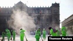 Un grupo de trabajadores desinfecta la plaza del Zócalo, en Ciudad de México, una de las ciudades más afectadas por la pandemia en la región.