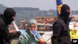 Silvia Romano acungerewe n'abajejwe umutekano agishika ku kibuga c'indege i Roma mu Butaliyano. Kw'italiki 10/05/2020.