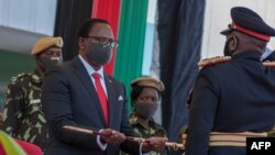 Malawi President-elect Lazarus Chakwera receives a sword of office as commander-in-chief of the Malawi Armed Forces during his inauguration at the Kamuzu Baracks, the Malawi Defence Force Headquarters, in Lilongwe, July 6, 2020.