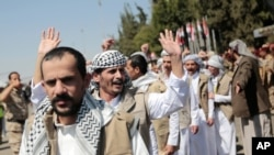 Yemeni prisoners gesture after being released by the Saudi-led coalition, during their arrival at the airport in Sanaa, Yemen, Oct. 15, 2020.