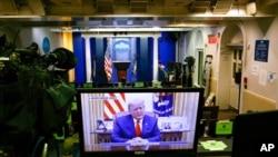 Slika na monitoru pokazuje predsjednika SAD Donalda Trumpa koji govori u videu postavljenom na Twitter nalogu Bijele kuće, u praznoj sali za brifinge Bredy, u Bijeloj kući, 13. januara 2021.