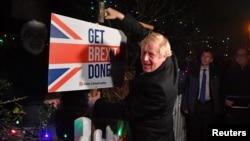 """Archivo - El primer ministro británico Boris Johnson posa con un almádena tras golpear un cartel que dice """"Hagan el Brexit"""" en South Benfleet, Gran Bretaña, el 11 de diciembre de 2019."""