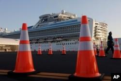 A security guard stands near the quarantined Diamond Princess cruise ship in Yokohama, near Tokyo, Feb. 13, 2020.