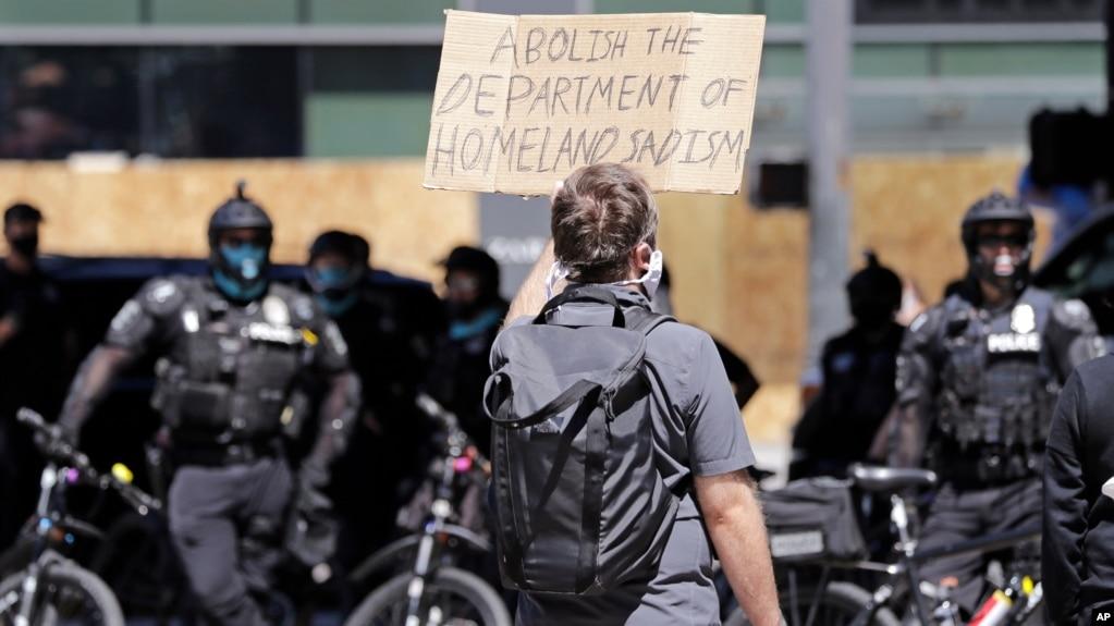 Një protestues mban një parrullë kundër forcave federale në Seattle