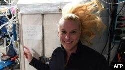 """Na fotografiji koju je NASA objavila na Twitteru 22. oktobra 2020. vidi se članica posade Međunarodne svemirske stanice Kate Rubins kako pokazuje znak na kome piše """"glasačka kabina Međunarodne svemirske stanice"""" (Foto: AFP)"""