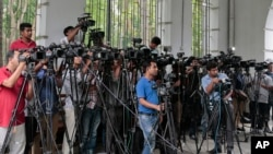 FILE - Reporters cover proceedings outside a court in Dhaka, Bangladesh, May 3, 2016. A Bangladeshi journalists group is expressing outrage over the recent detention and one year sentence given to Bangla Tribune correspondent Ariful Islam.