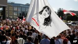 2020年8月17日白俄罗斯首都明斯一次集会上人们举着印有反对派候选人斯维特兰娜·季哈诺夫斯卡娅肖像的旗帜。