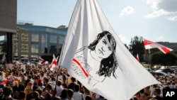 People hold a flag with a portrait of Sviatlana Tsikhanouskaya, former candidate for the presidential elections, during a rally in Minsk, Belarus, Aug. 17, 2020.