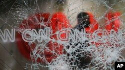 A security guard walks behind shattered glass at the CNN building at the CNN Center in the aftermath of a demonstration against police violence on Saturday, May 30, 2020, in Atlanta. (AP Photo/Brynn Anderson)