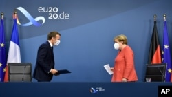 German Chancellor Angela Merkel, right, and French President Emmanuel Macron prepare to address a media conference at the end of an EU summit in Brussels, Tuesday, July 21, 2020. Weary European Union leaders finally clinched an unprecedented budget