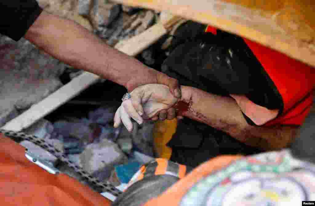 Un rescatista sostiene la mano de una víctima entre los escombros en el lugar de los ataques aéreos israelíes, en la ciudad de Gaza.
