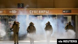 FILE - Russia's Emergencies Ministry members wearing personal protective equipment spray disinfectant near a gift kiosk at the Kievsky Railway Station in Moscow, May 18, 2020.