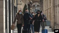 Mujeres que usan mascarillas faciales como precaución contra el coronavirus caminan en la rue Rivoli en París, el viernes, 6 de noviembre de 2020.