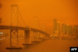 FILE - The San Francisco Bay Bridge and city skyline are obscured in orange smoke and haze as seen from Treasure Island in San Francisco, Calif., Sep. 9, 2020.