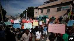 FILE - Several hundred protesters march carrying signs in Creole calling for President Jovenel Moïse to resign, in Port-au-Prince, Haiti, Oct. 21, 2019.