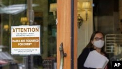 FILE - A sign reminds customers to wear masks at a bakery in Lake Oswego, Oregon, May 21, 2021. Oregon Gov. Kate Brown on Aug. 10 announced a statewide indoor mask requirement due to the spike in COVID-19 hospitalizations and cases.