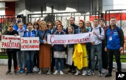 """Journalists of Belarusian TUT.BY media outlet hold banners reading """"I'm not protesting; I'm working"""", """"This is me at work"""", """"Freedom for journalists!"""", from left to right, as they stand in front of a police station in Minsk, Belarus, Sept. 2, 2020."""