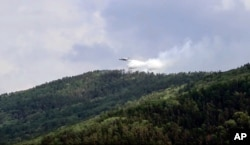 FILE - In this July 10, 2020 file image taken from video provided by Russian Emergency Ministry, a Russian aircraft releases water in the Trans-Baikal National Park in Buryatia, southern Siberia.