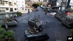 Lebanese army soldiers sit on their armored vehicles as they deployed to contain tensions after a shootout during a funeral procession in the town of Khalde, south of Beirut, Lebanon, Aug. 1, 2021.